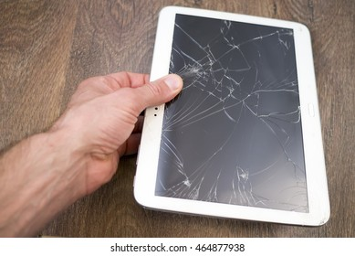 Man's hand  holds tablet PC with broken touchscreen