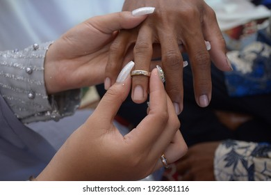 a man's hand inserts the ring into the finger of the bride. wedding photo concept