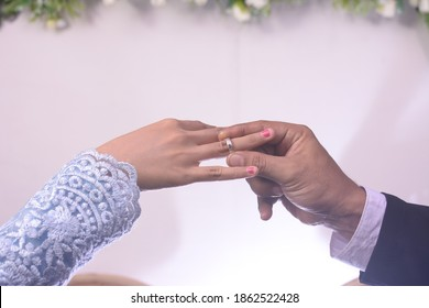 a man's hand inserts a ring on the finger of the bride