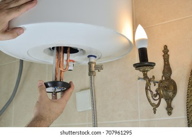 Man's hand installing a new water heater in a boiler