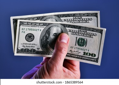 A man's hand isolated on a blue background shows  200 dollars in two 100 dollar bill