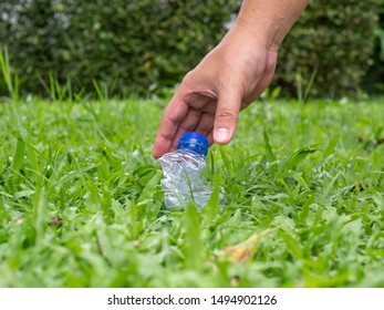 Man's hand keeps plastic bottles left on green grass. Plastic waste is bad for global warming.
