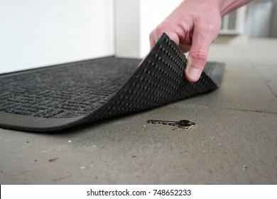 A man's hand is lifting up doormat to revealing a key hidden under