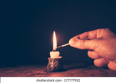 Man's hand is lighting a candle