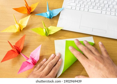 A man's hand looking at a computer and making origami