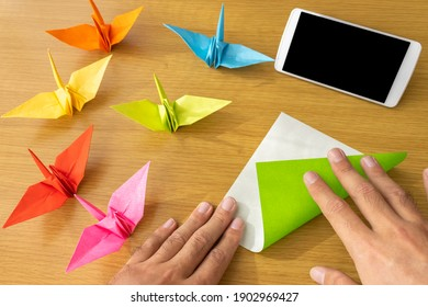 A man's hand looking at a smartphone and making origami