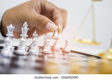 Man's hand making the first move in a chess game. Business concept.