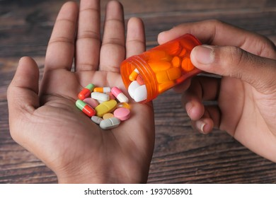 man's hand with medicine spilled out of the pill container
