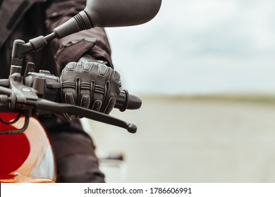 Man's hand in motorcycle protective gloves holds a motorcycle, close-up