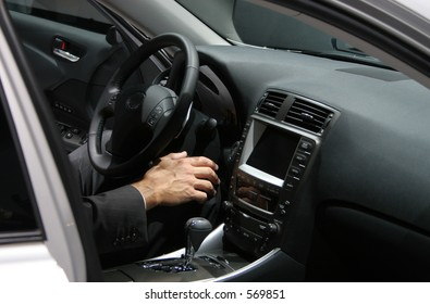 man's hand in new car interior, man wearing a business suit