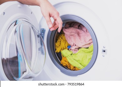 Man's hand next to a washing machine with clothes. Washing clothes in the laundry. Washing machine drum with washed wet clothes. Washing machine in the laundry. Daily routine