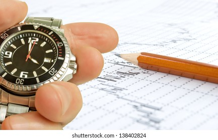 Man's hand on a background of the exchange graph with a pencil.