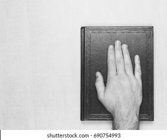 man's hand on the book, the oath on the Bible. top view closeup. black and white photo. mock up for text, phrases, lettering