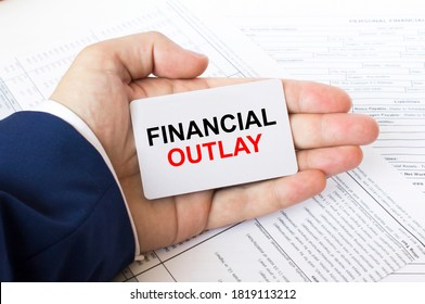 A man's hand is on the financial tables holding a business card with the inscription Financial Outlay. Business concept photo