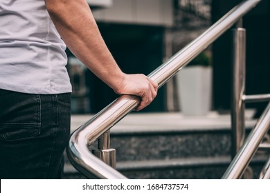 man's hand on the railing, a man in a white T-shirt and black jeans. go upstairs. outside