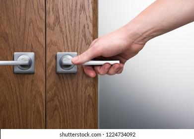 A man's hand on a steel door handle. Swinging interior door. Dark oak texture. Frosted glass