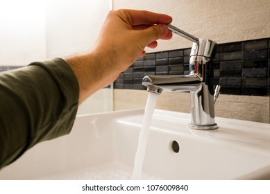 a man's hand opens a tap-water faucet in the bathroom