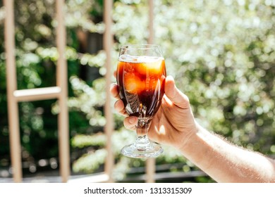 Man's  hand outside holding glass of black cold brew coffee with ice