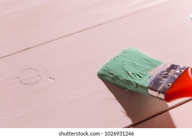 man's hand paint brush with green paint on white wooden table