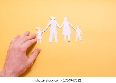 A man's hand with a paper-cut silhouette of a family with a father, mother, son and daughter on a yellow background. The concept of family, parents, children, love, care
