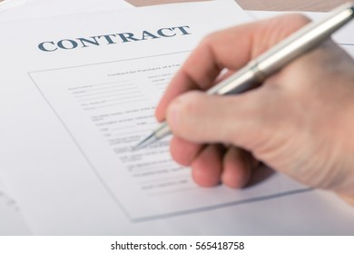 man's hand with a pen sign a contract