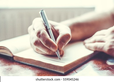Man's hand with a pen writes the task in notebook on a wooden table. Modern style.