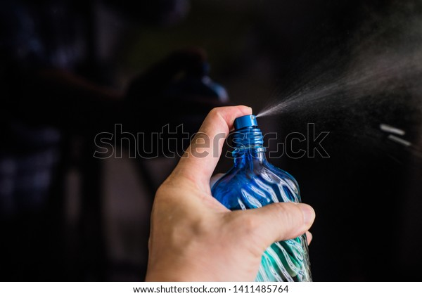 man's hand with perfume bottle