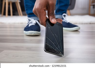 Man's Hand Picking Up Mobile Phone With Broken Screen