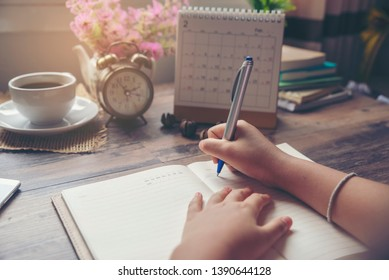 Man's hand planner writing diary, agenda calendar, daily appointment, and mark and note schedule (meeting) on organizer book by pen at home office. Planner concept.