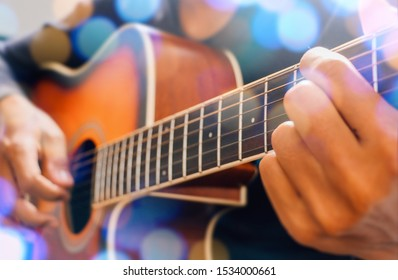Man's hand playing acoustic guitar, close up