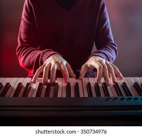Man's hand playing piano.