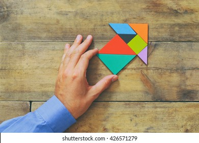 man's hand pointing at arrow made from square tangram puzzle, wooden background