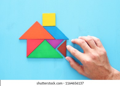 man's hand pointing at house made from tangram puzzle over wooden table