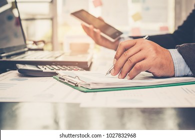 A man's hand pointing a pen at graph,chart and using calculator for analyzing investment in his office.