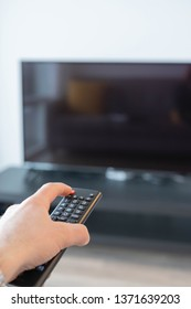 Mans hand pointing a TV remote at a switched off TV