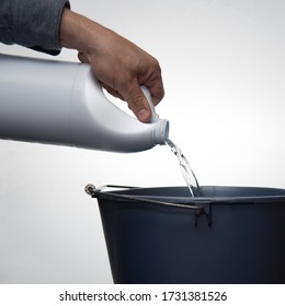 A man's hand pouring cleaner or bleach into a blue bucket against a white background.