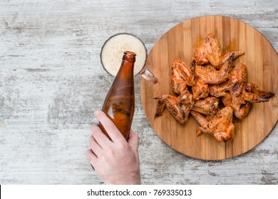 a man's hand pours beer from a bottle into a mug near fried chicken wings. Top view