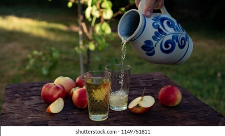 a man's hand pours Traditional apple wine in a refilled glass in the city of Frankfurt. A jug of wine on an old wooden table in the garden, around it apples