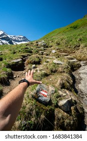 Mans hand pov with watches austria tourist mark hiking mountain alps covered with snow in summer