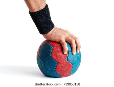 Man's hand pressing down on blue and red handball isolated on white
