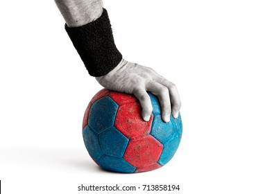 Man's hand pressing down on blue and red handball isolated on white, colored handball, desaturated hand