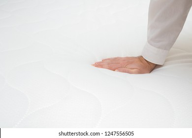 Man's hand pressing on white mattress. Checking hardness and softness. Choice of the best type and quality. Copy space. Empty place for text or logo. Side view. Close up.