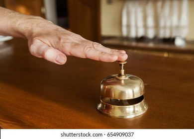 Man's hand is pressing service bell in a hotel