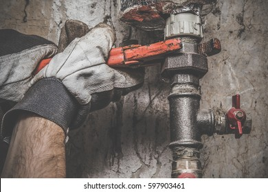 Man's hand in protective glove working with wrench at pipe. Plumbing. Vintage style.
