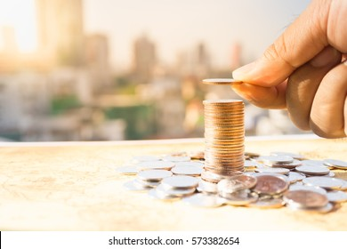 Man's hand put money coins to stack of coins. Money, Financial, Business Growth concept.