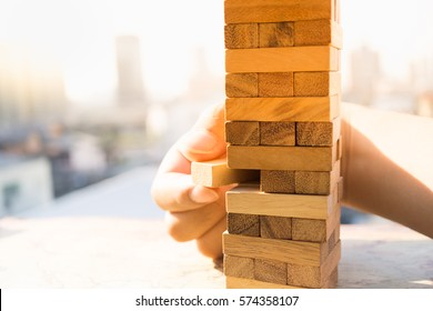 Man's hand put one block to the tower stack from wooden blocks toy with public park background