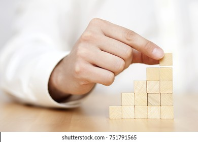 Man's hand put wooden blocks in the shape of a staircase. Business success concept.