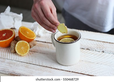 Man's hand puts ginger tea on a light background. The concept of health.