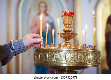 a man's hand puts a lighted candle in front of the icon of the Russian Orthodox Church