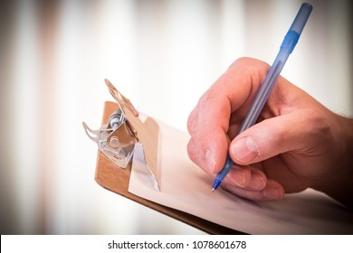 Man's hand puts pen to paper on a clipboard, to sign a form, make a list, or fill out information.